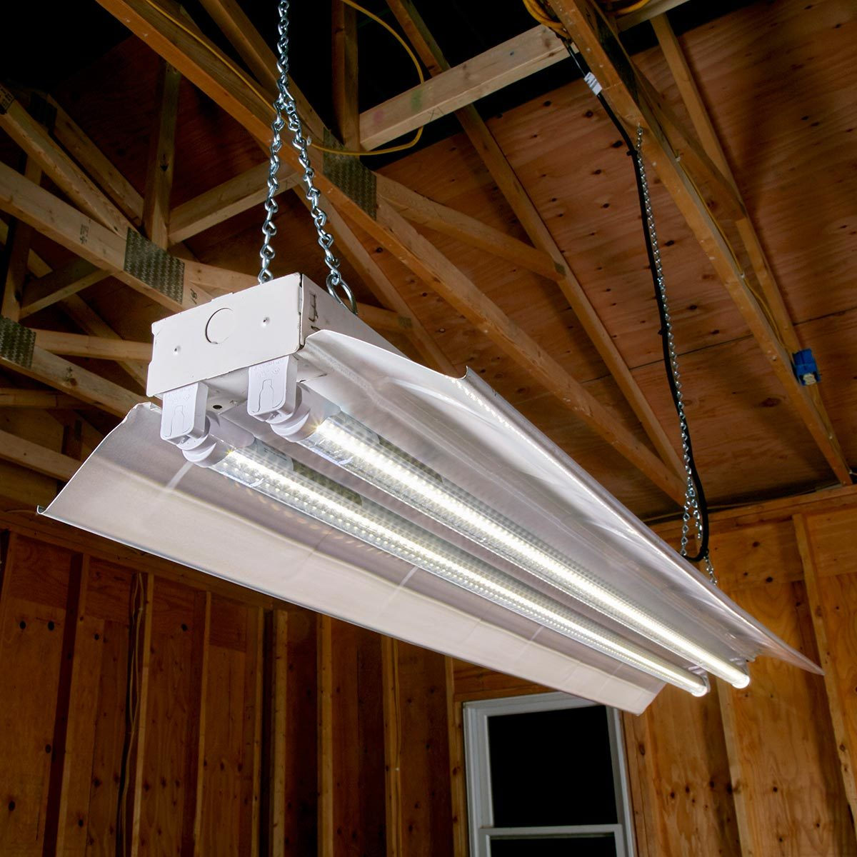 traditional fluorescent shop light fixtures are designed to accommodate  4-ft fluorescent tubes, which, compared to incandescent bulbs, provided  longer